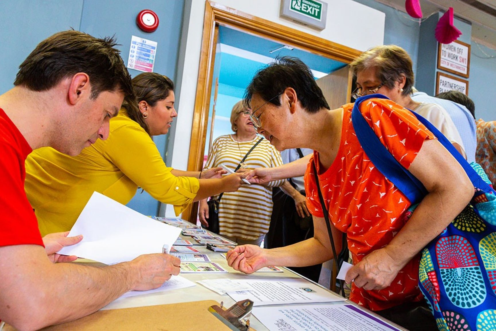 Registration at an event. Two people are signing in attendees, everyone is wearing brightly coloured clothing.