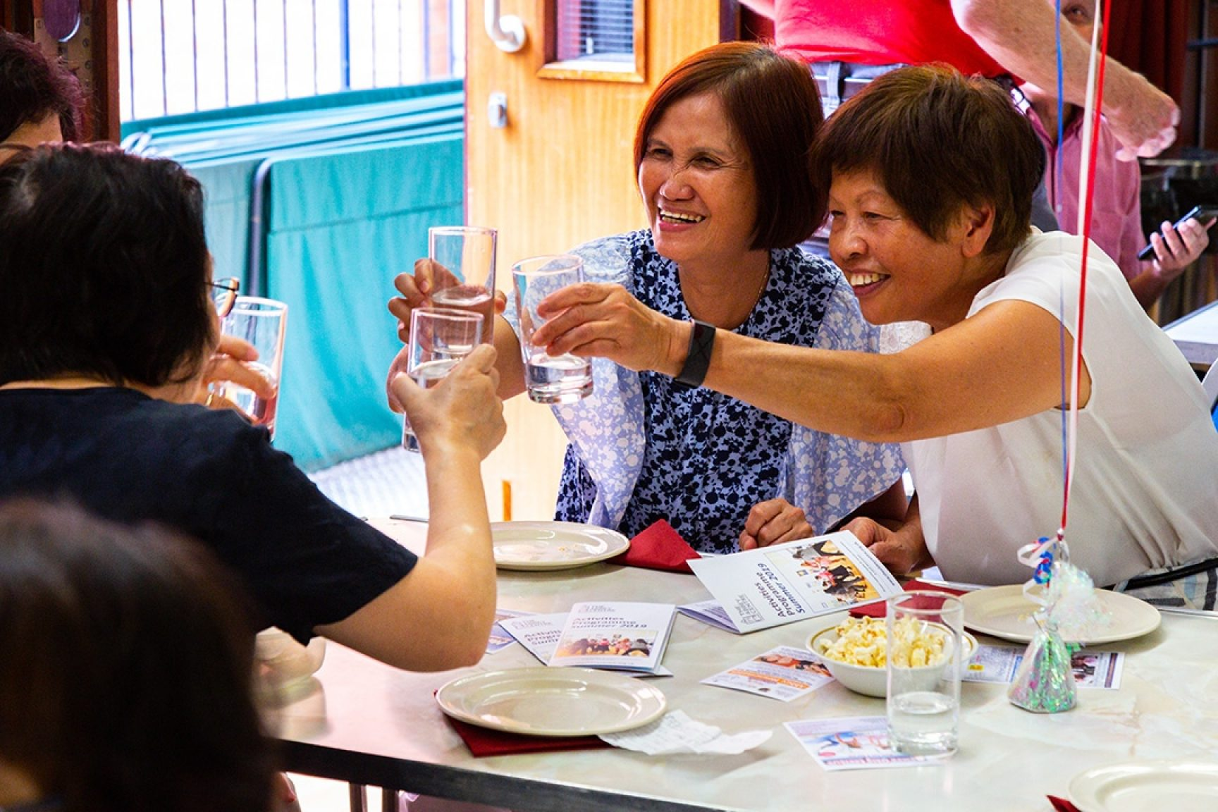 Several women around table  enjoying themselves and raising a glass at a fun community event.