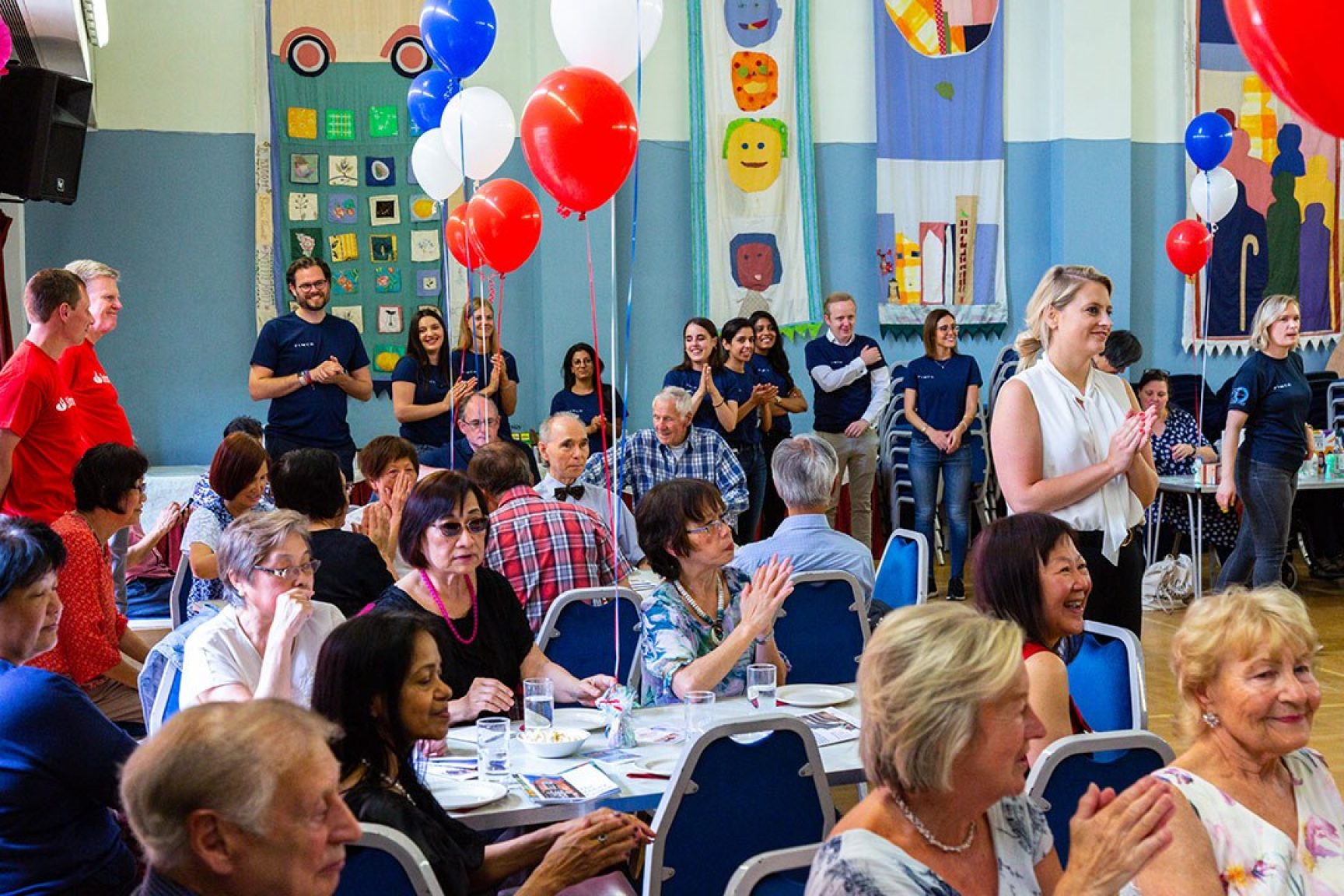 A community event, there are balloons tied to chairs, and people are looking at something off camera. People are smiling and looking really happy.