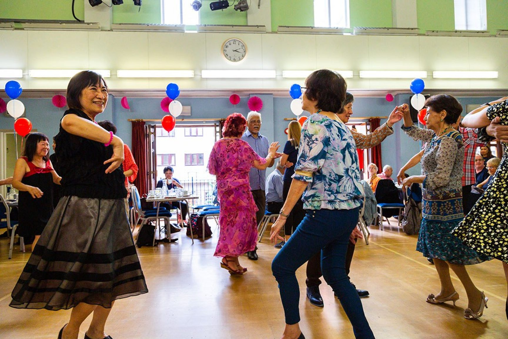 A dancing event at a community space. There are various women dancing, and the space is decorated with balloons.
