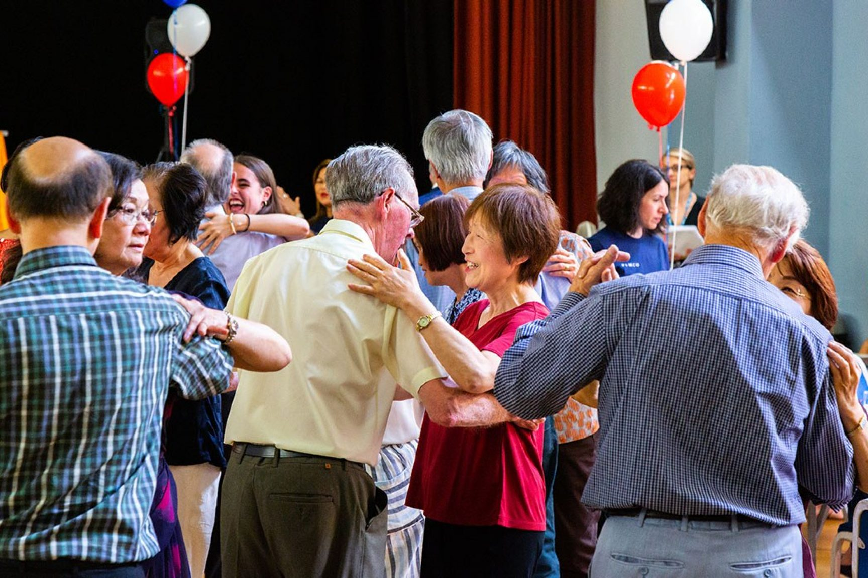 There are older couples dancing at a community space. Balloons are decorating the space.