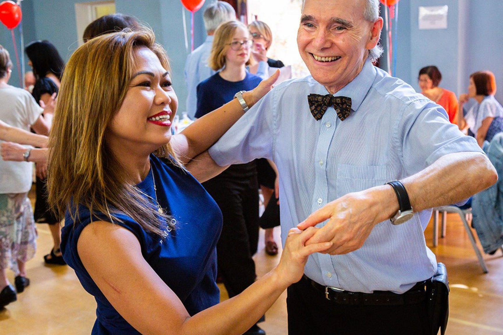 A female volunteer is dancing with an older man at a community event, they are both smiling and having fun.