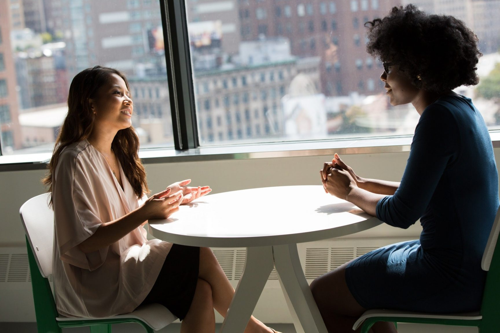 Two women talking to each other over a table