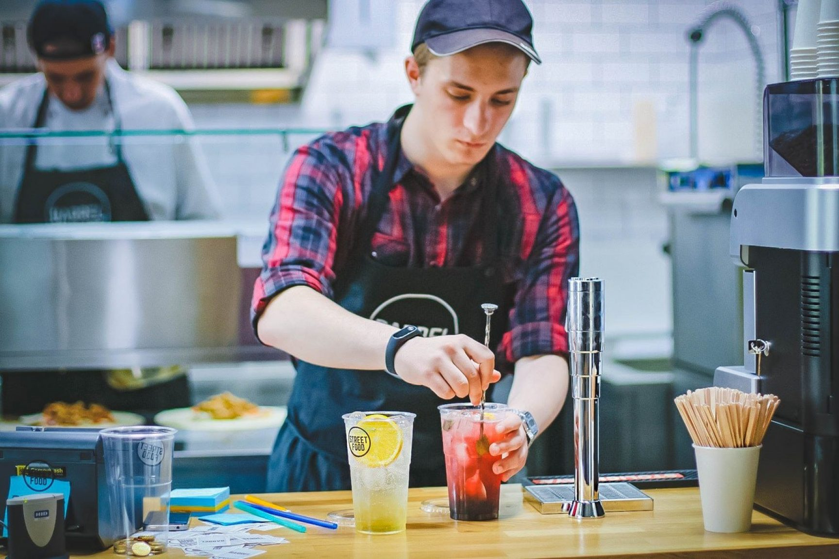 A person mixing drinks behind a counter. He is wearing a cap and an apron.