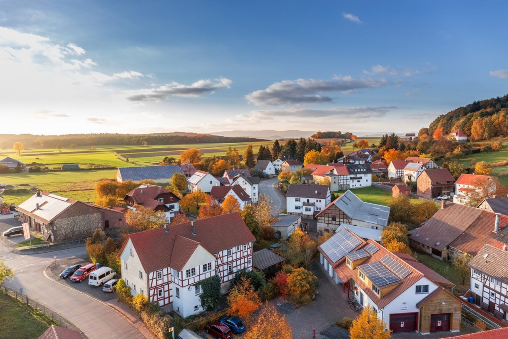 An aerial view of a small village in the countryside. The sun is rising in the distance.