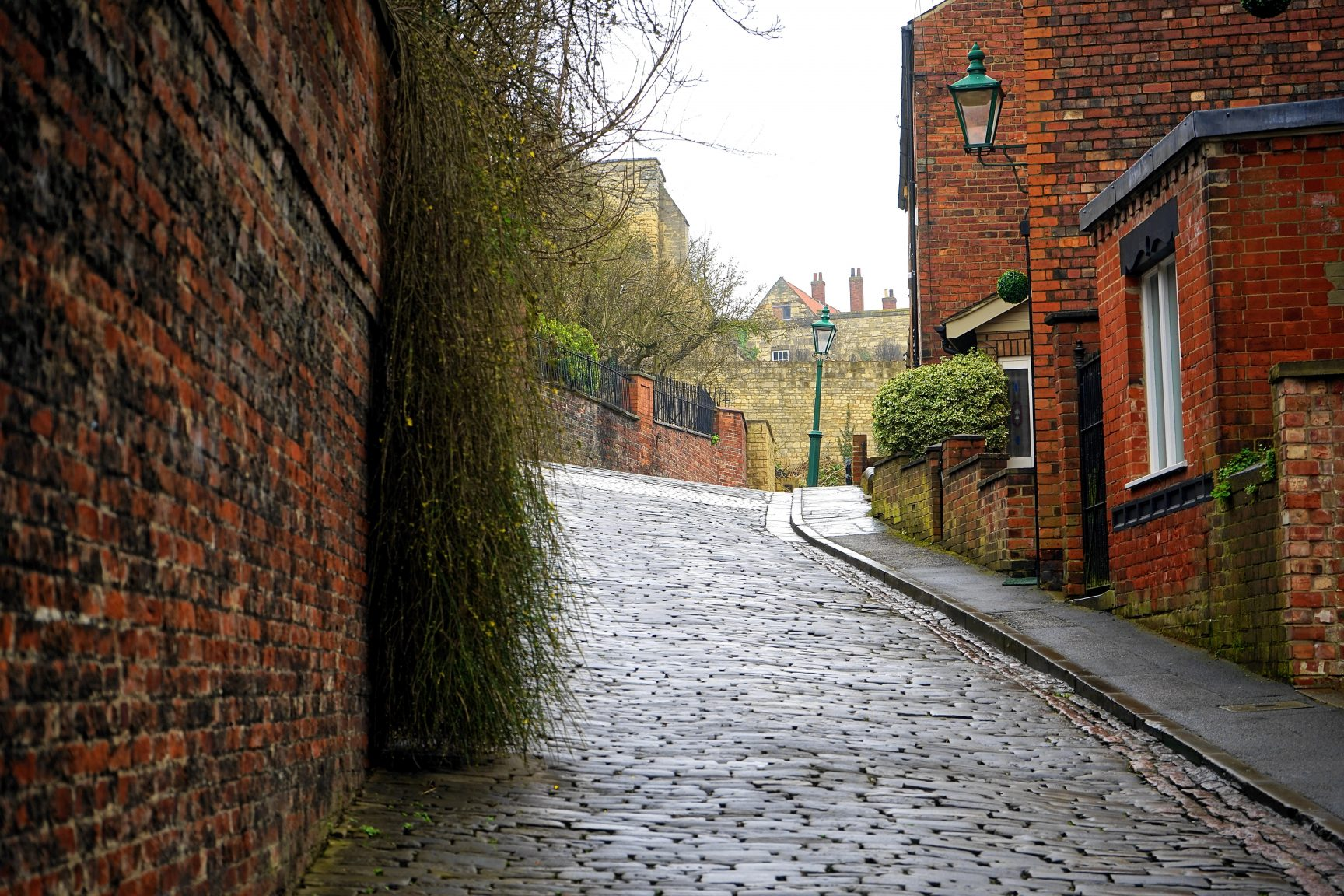 A small cobbled street, with red brick houses. It's a grey day and the street is damp.