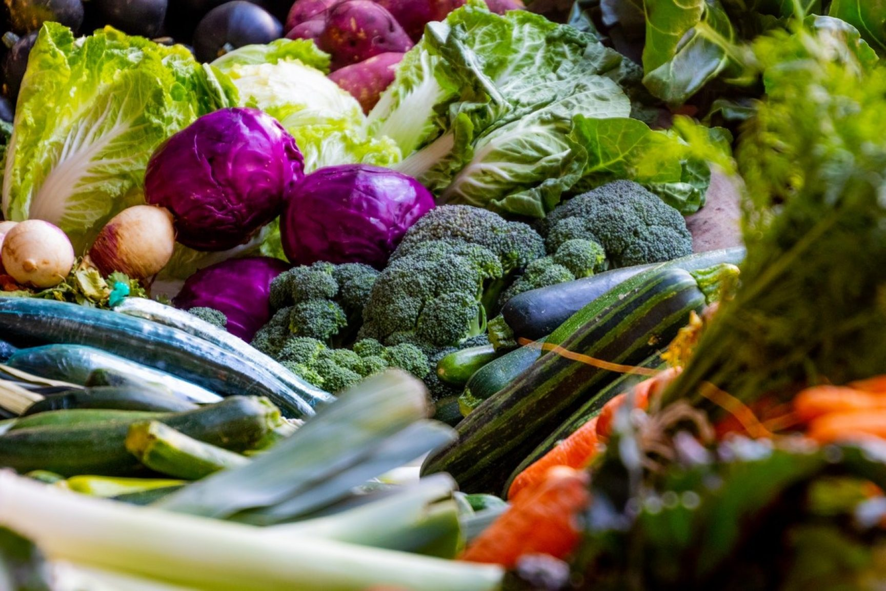 Lots of vegetables are spread out beautifully on a table, there is broccoli, cabbage, leeks, courgette, potatoes and more.
