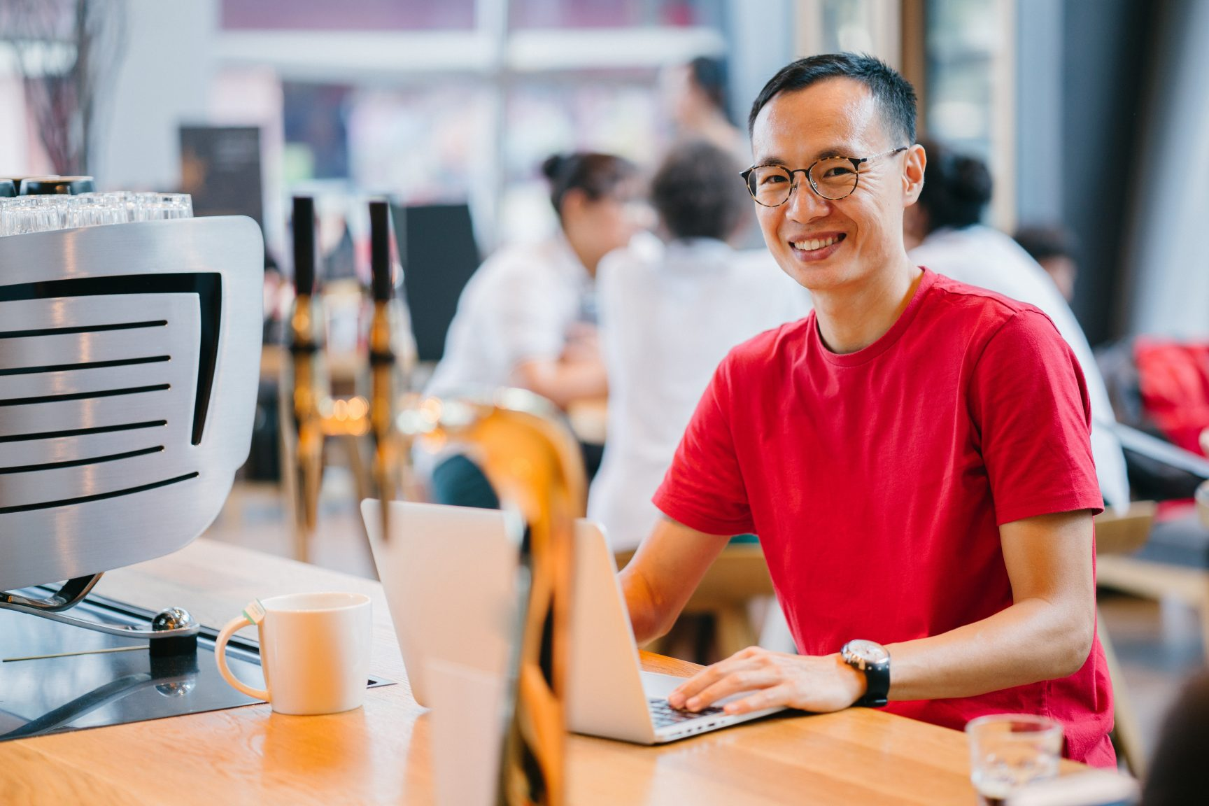 A man wearing glasses in a red t-shirt at a coffee shop working at a laptop. He is smiling at the camera.