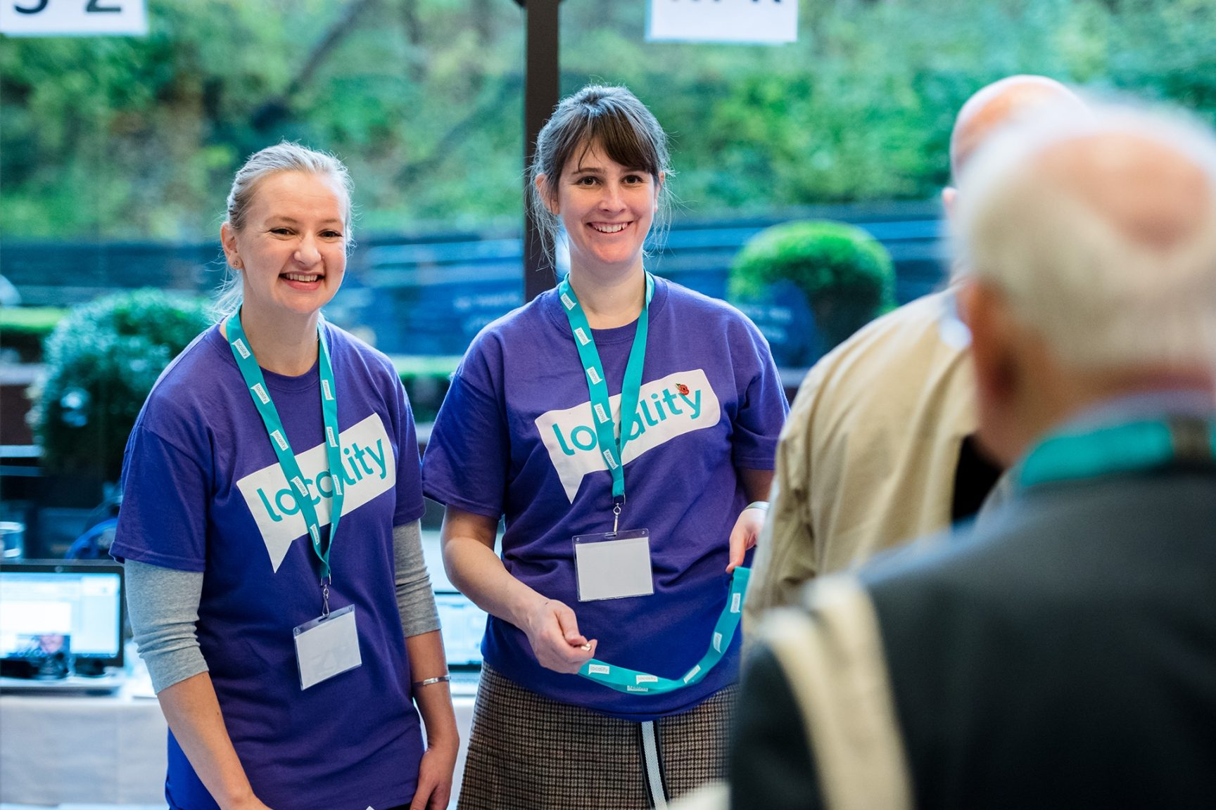 Two members of Locality wearing Locality t-shirts at an event