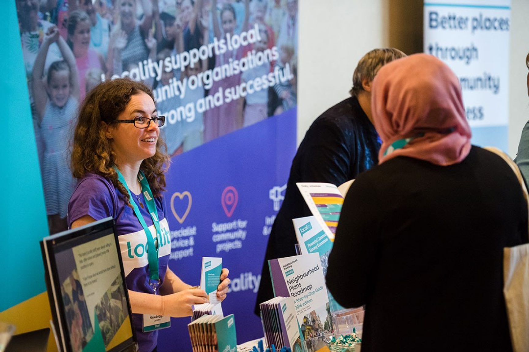 A Locality staff member at a Locality event stand chatting to someone. The Locality staff member is smiling.