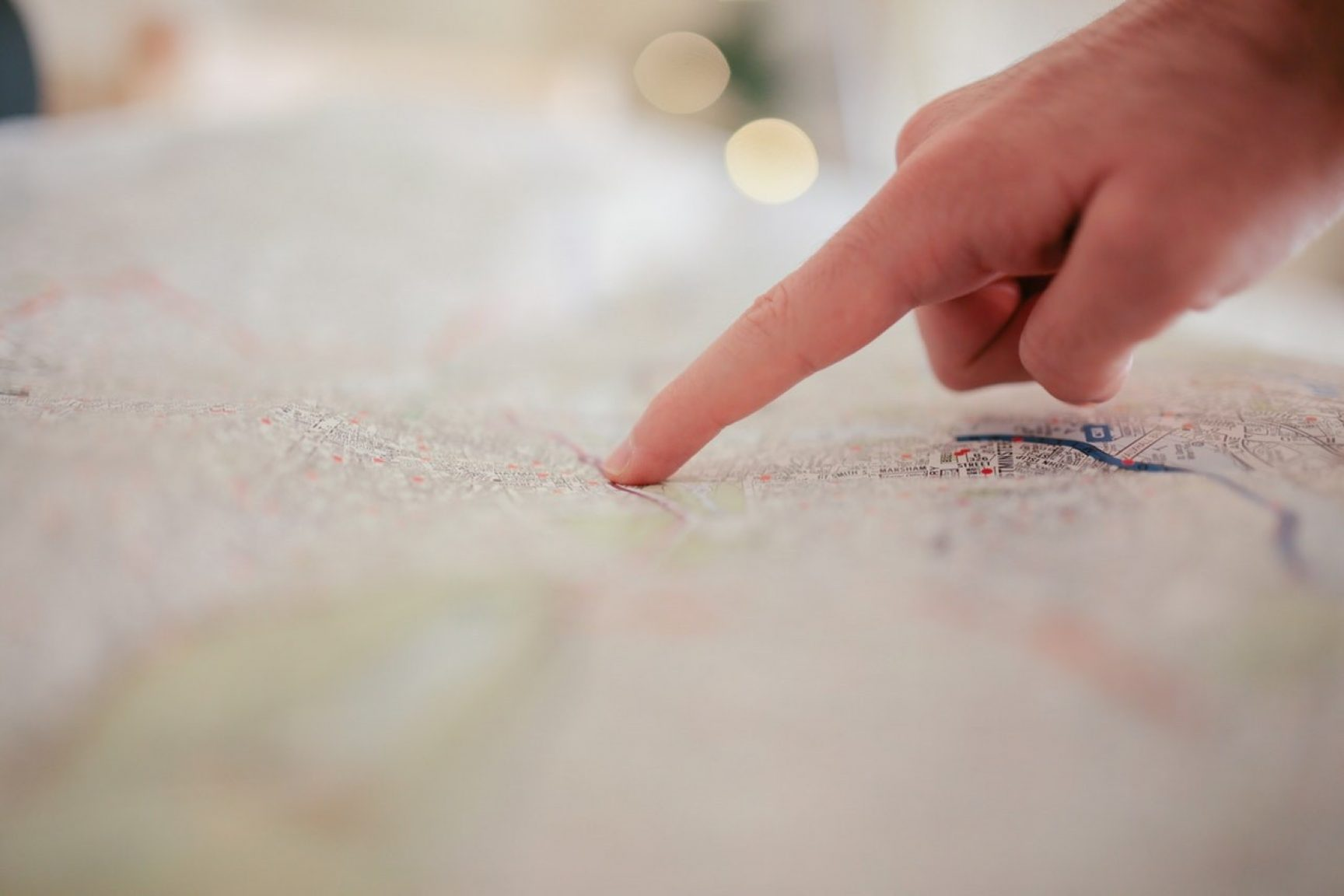 A hand pointing to something on a map.