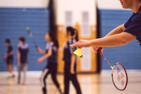 A person about to take aim and serve in a badminton game. There are other games of badminton happening in the background.