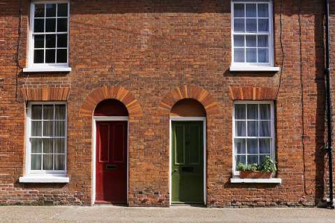 Two red brick terraced houses. One has a red front door, and the other has a green front door.