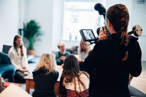 Someone filming a group of people in a room. They are seated comfortably.